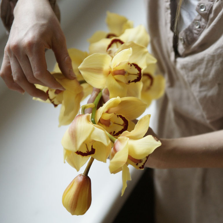 Close up of a woman holding a yellow orchid.